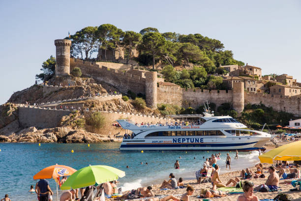 Beach under the castle in Tossa de Mar. People on the seafront near the walls of the old city. The historic city and the castle tower of La Vila Vella. A beautiful Catalan town on the Costa Brava – zdjęcie