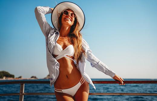 Beach vacation. Beautiful happy woman in sunhat and bikini enjoying summer trip