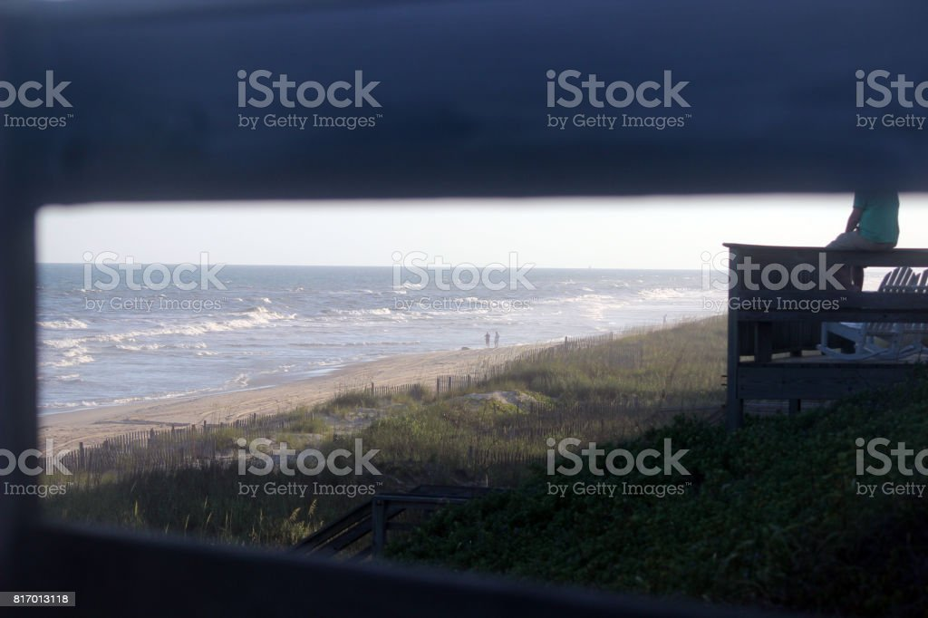 Beach Vacation Scene Viewed Through Deck Railing stock photo