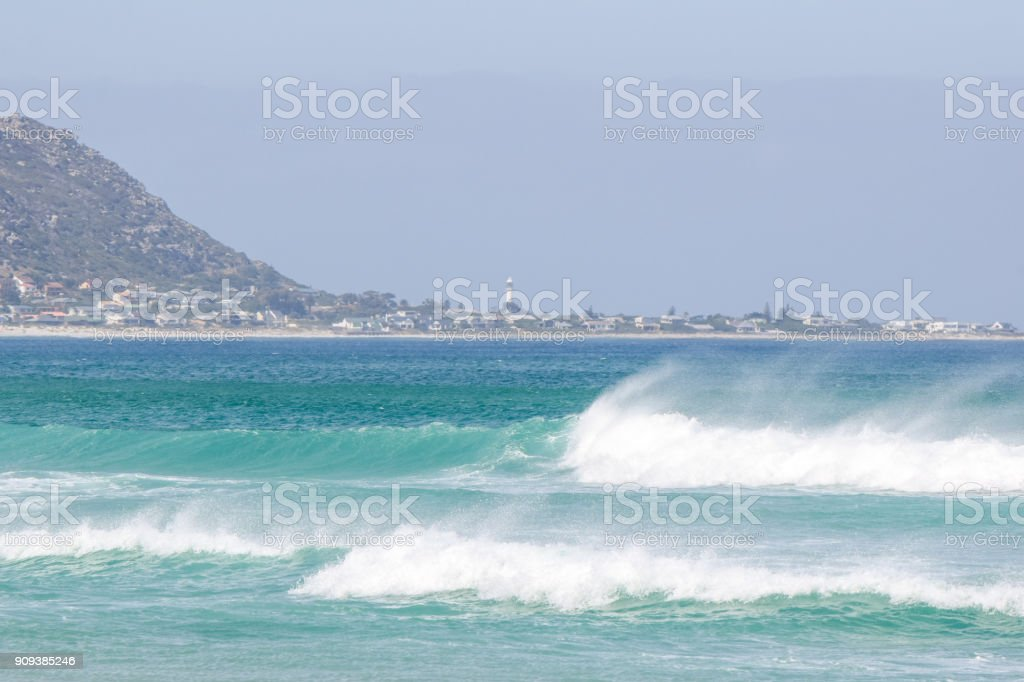 Beach view of the towns of Kommetjie and Klein Slangkop on the Cape Peninsula near Cape Town, South Africa, seen from Noordhoek Long Beach. Beautiful waves and spray in the foreground. stock photo