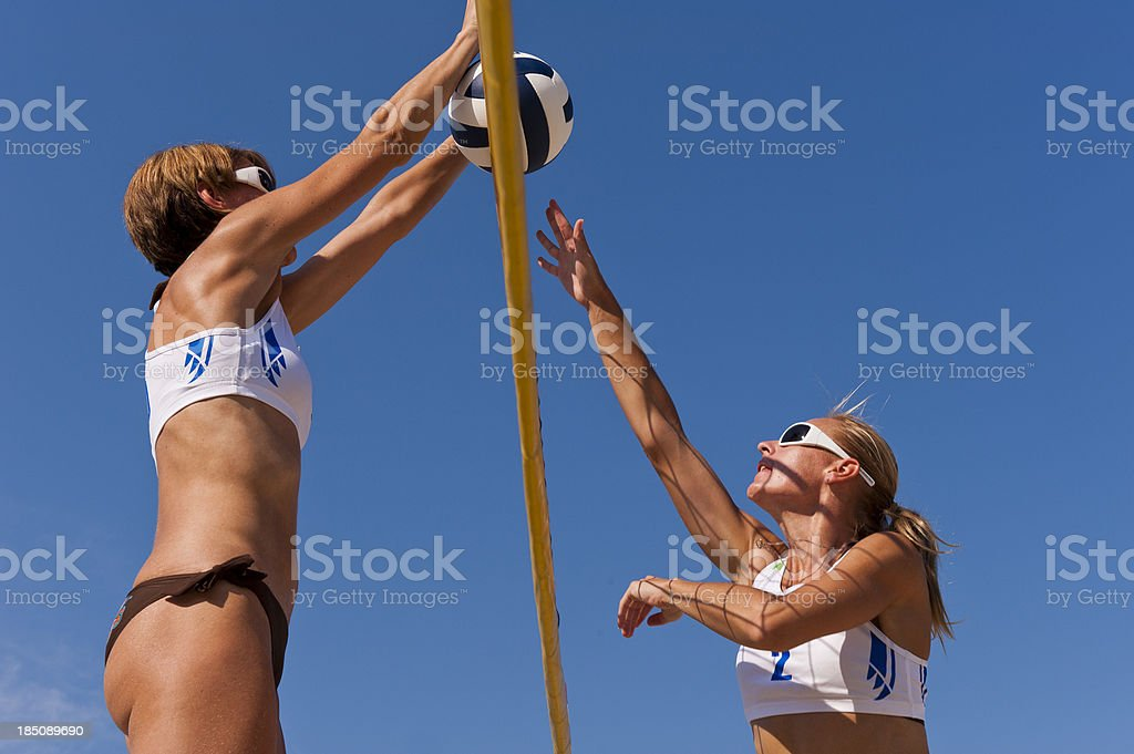 Side view of two attractive female volleybal players in defensive and...