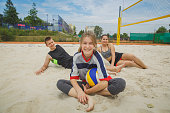 Beach volleyball amateur players happy after the game at summer day under sky.