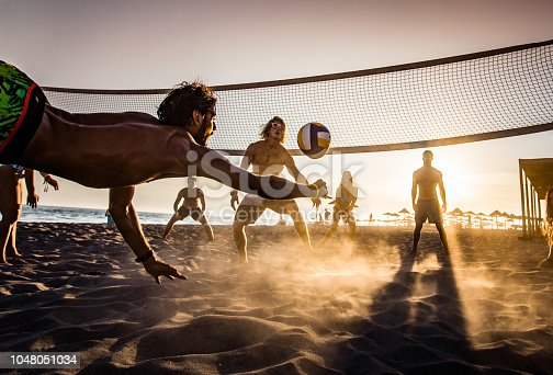 Group of young people having fun while playing beach volleyball in summer day at sunset.