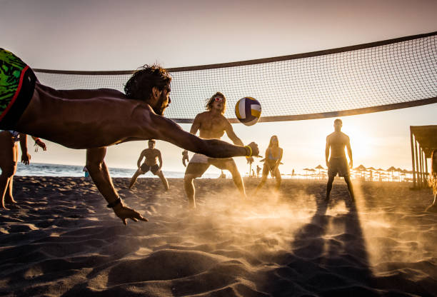 Beach volleyball at sunset! Group of young people having fun while playing beach volleyball in summer day at sunset. leisure equipment stock pictures, royalty-free photos & images