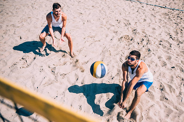 beach volleyball competition, men playing - volleyball stock photos and pictures