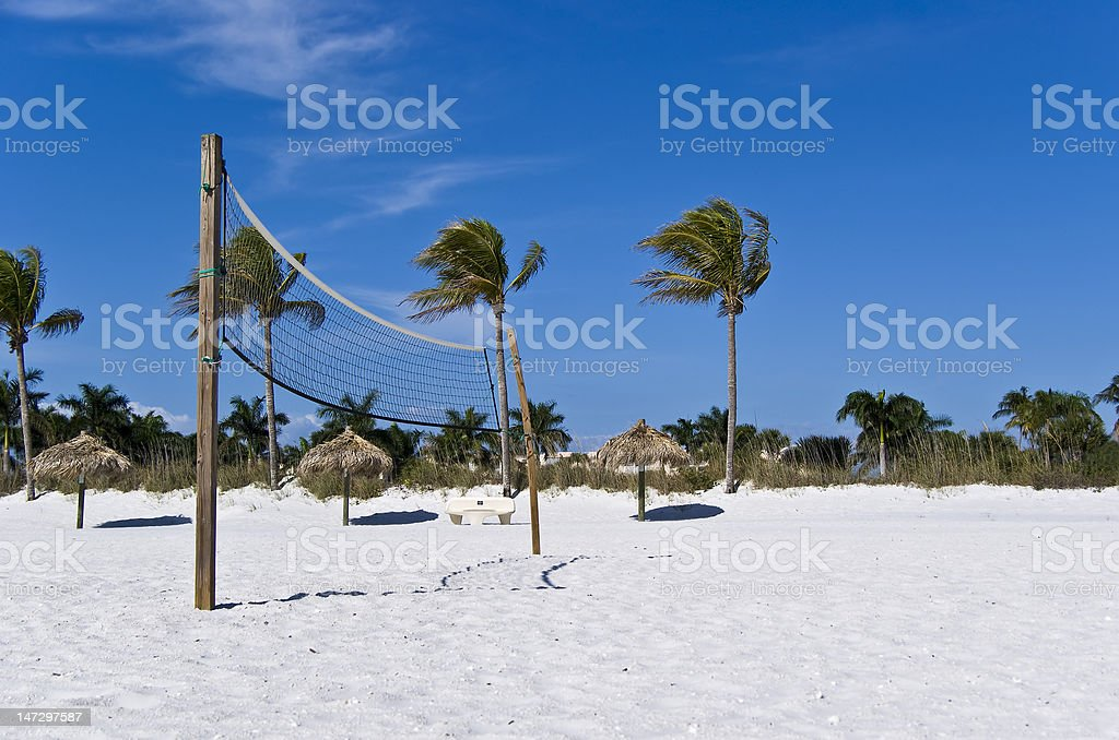 Beach volleyball net with palm trees and palapas royalty-free stock photo