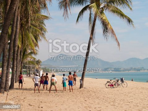 Nha Trang, Vietnam - March 18, 2006: Game of Beach Volleyball is played on the beach in Nha Trang, Vietnam by some locals. A net is strung between some palm trees. Nha Trang is a popular beachside destination for Asian visitors.
