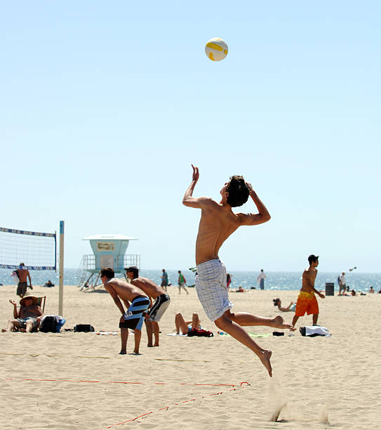 Beach Volleyball High Flying Serve In Beach Volleyball Match spiked stock pictures, royalty-free photos & images