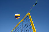 Beach volleyball personal perspective close-up of net and ball under clear blue sky. Taken with blurred motion and copy space.