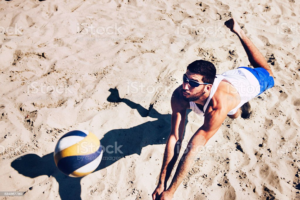Beach volleyball player jumping for ball stock photo