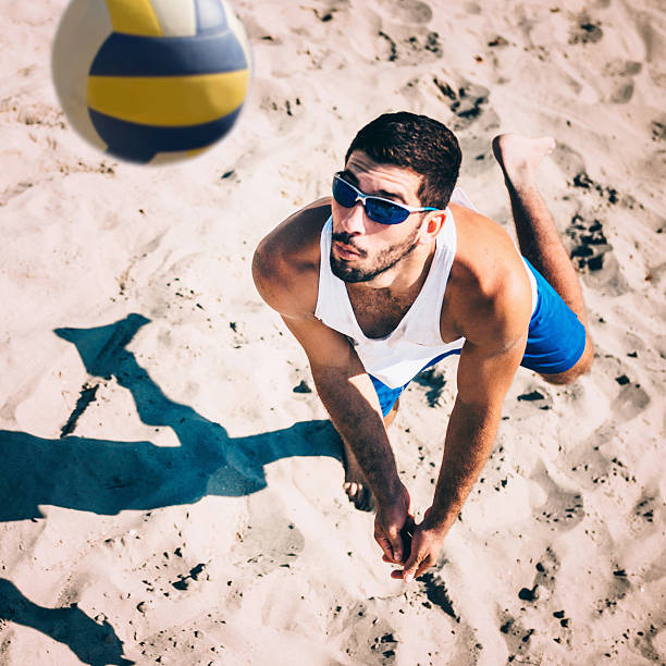 beach volleyball player receiving the ball, action shot - volleyball sport stock photos and pictures