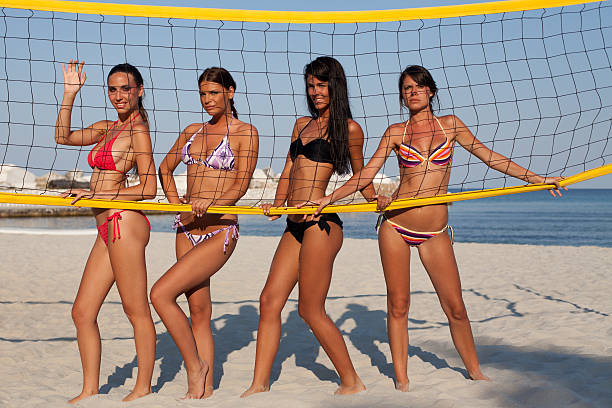 Beach volleyball players posing behind the net stock photo