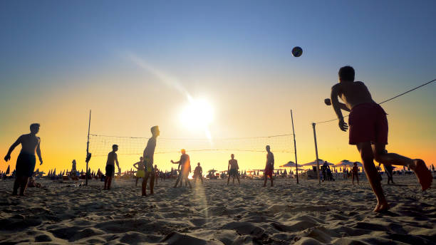 Beach volleyball silhouette during sport recreation at summer vacationat sunset stock photo