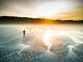 Aerial shot of a solitary woman walking between tide pools on a beach at Moclips, Grays Harbor County, WA, as the sun rises over the trees on a cloudy, hazy day.