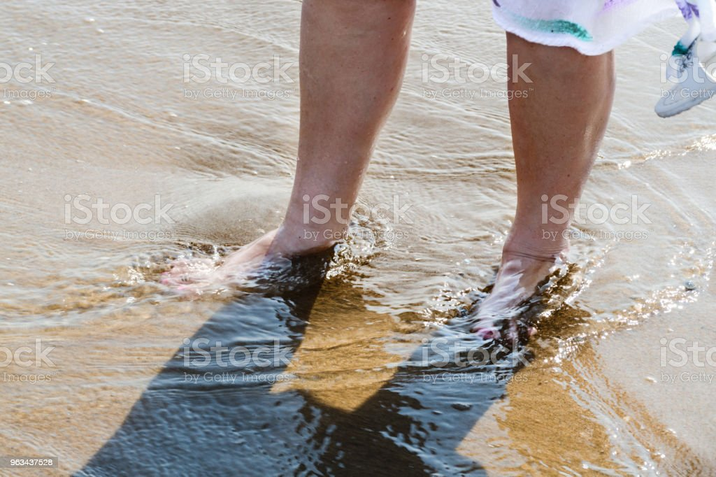 Beach walk, legs of a woman in the water stock photo