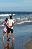 A happy couple walks on a sunny beach.