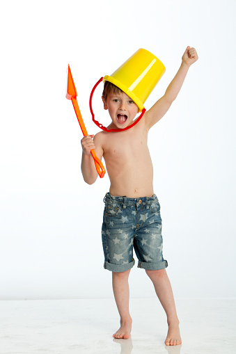 Little boy imitating a warrior with a bucket and spade