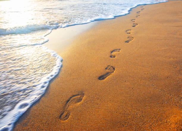 Strand, Welle und Fußabdrücke bei Sonnenuntergang – Foto