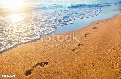istock beach, wave and footprints at sunset time 538323908