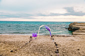 Wedding set up with bamboo marriage ceremony arch ornated with purple balloons, tulle textile, stone ways and candles on tropical beach for outdoor wedding reception sun dawn time.