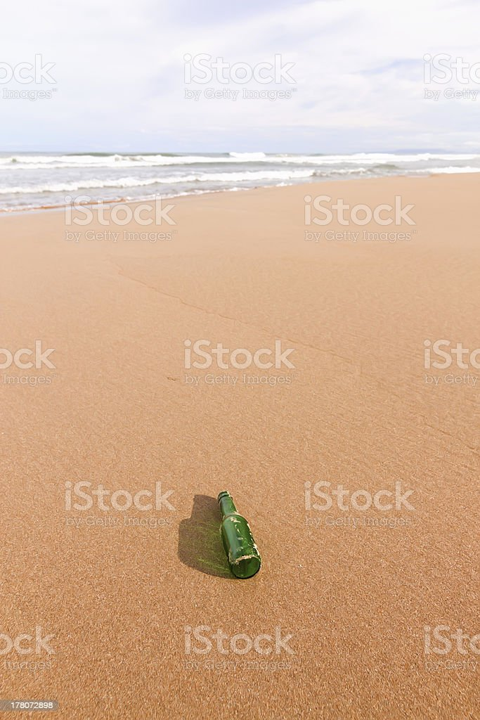 beach with a bottle in the foreground royalty-free stock photo