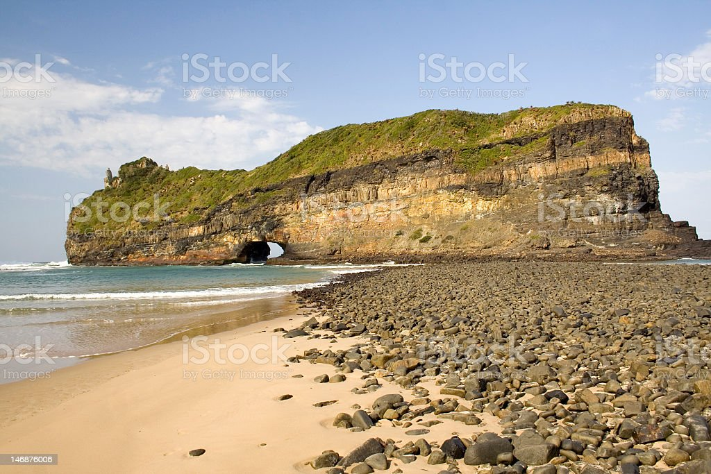 Beach with a rocky landscape in background stock photo