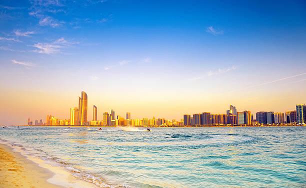 пляж с фоном абу-даби skyline at sunset - abu dhabi стоковые фото и изображения