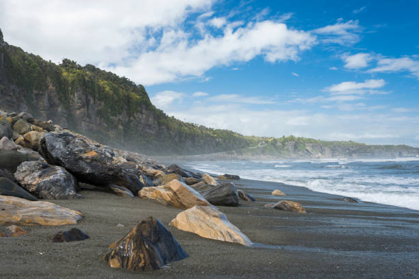 Beach with big boulders and blue sky at Punakaiki with the Tasman sea stock photo