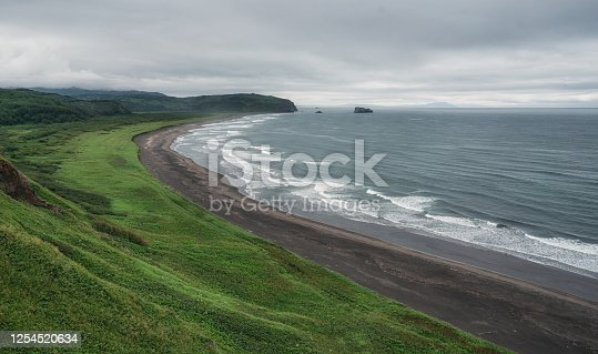 Beach with black sand and Waves in Pacific ocean shore on Kamchatka.