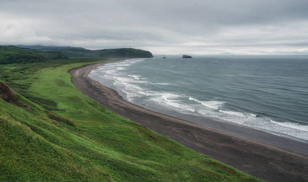 Beach with black sand and Waves in Pacific ocean shore on Kamchatka Beach with black sand and Waves in Pacific ocean shore on Kamchatka. kamchatka peninsula stock pictures, royalty-free photos & images