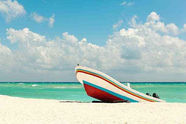 beach with fishing boat on caribbean sea, playa del carmen - playa del carmen stock photos and pictures