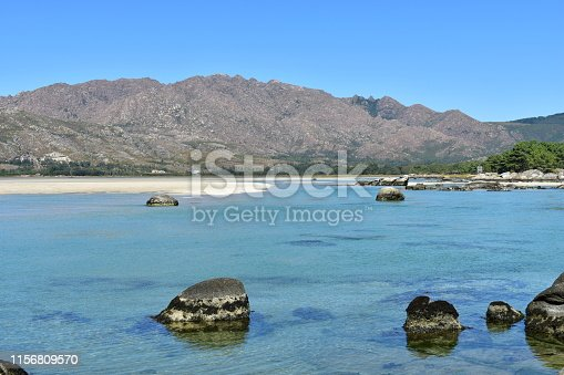 Carnota, A Coruña Province, Rias Altas, Galicia, Spain. Beach and mountain with lagoon and turquoise water. Clear sky, sunny day.