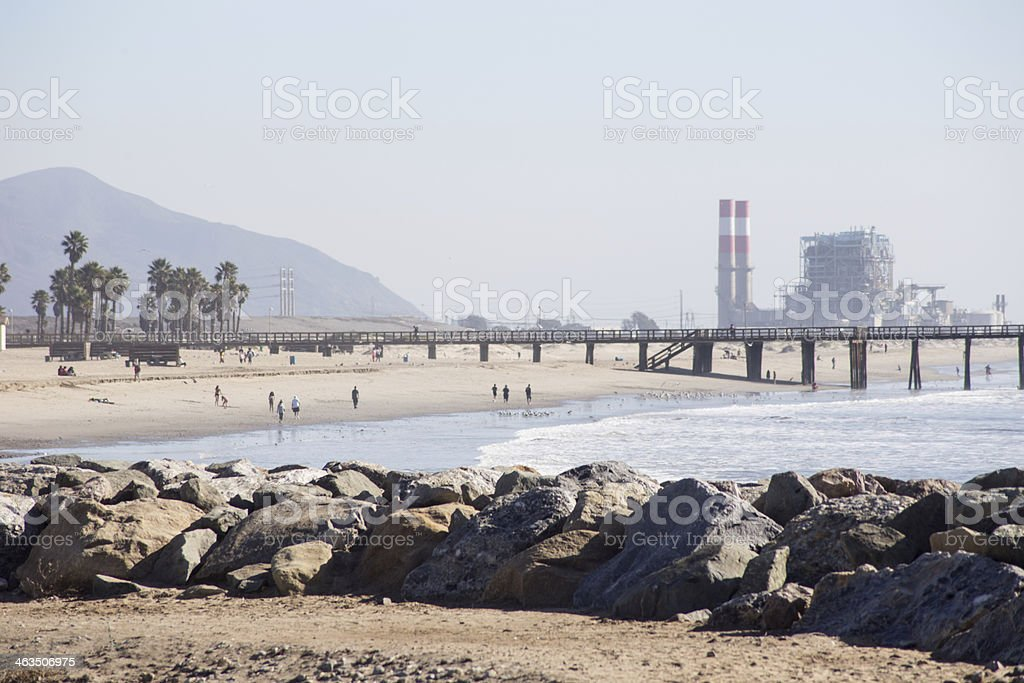 Beach with Pier and Power Plant in Background stock photo