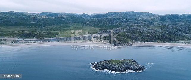 A beach with rocky hills. Tundra in the Russian north.