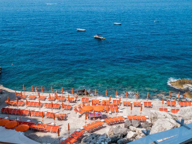 Beach with sunbeds at Praiano cliffs in the Amalfi coast, Italy. stock photo