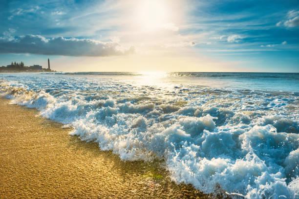 Strand mit Wellen und Maspalomas Leuchtturm im Hintergrund – Foto