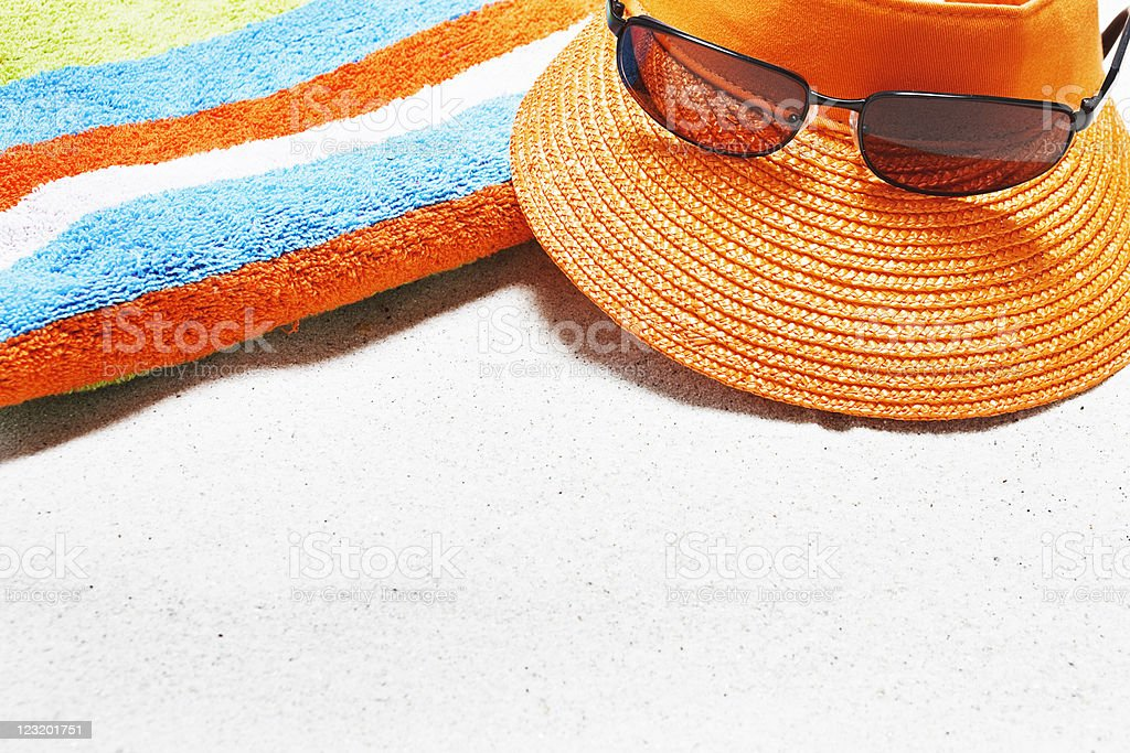 Beach with towel, sunglasses, sunscreen, shell, cap and copy space stock photo