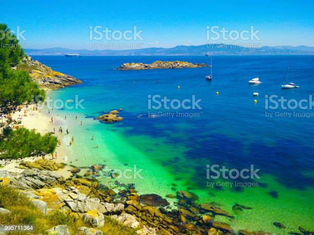 Photo of Beach with transparent green water in Cies Islands, in Galicia, Spain, with boats docked in front of