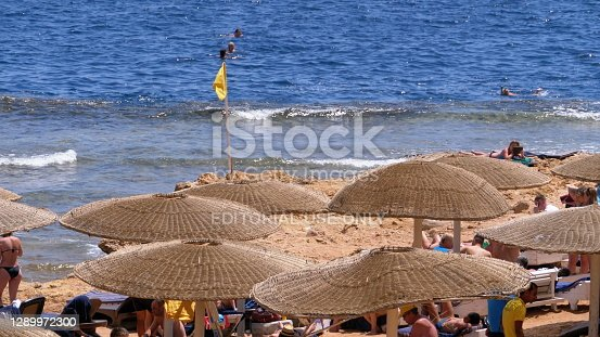 EGYPT, SHARM EL SHEIKH, APRIL 4, 2019: Beach with Umbrellas and Sunbeds in Egypt. Resort on Red Sea Coast. People relax and sunbathe on the seashore. Daytime panoramic view of the Sharm El Sheikh beach. The coastal resort line. The exotic landscape for relaxation.
