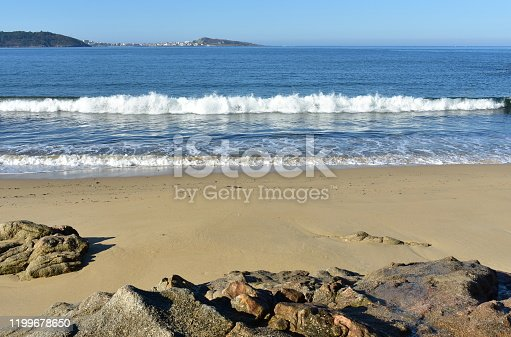 Muxia, Rias Altas, A Coruña Province, Galicia, Spain. Beach with waves and rocks on a sunny day. Blue sea with white foam.