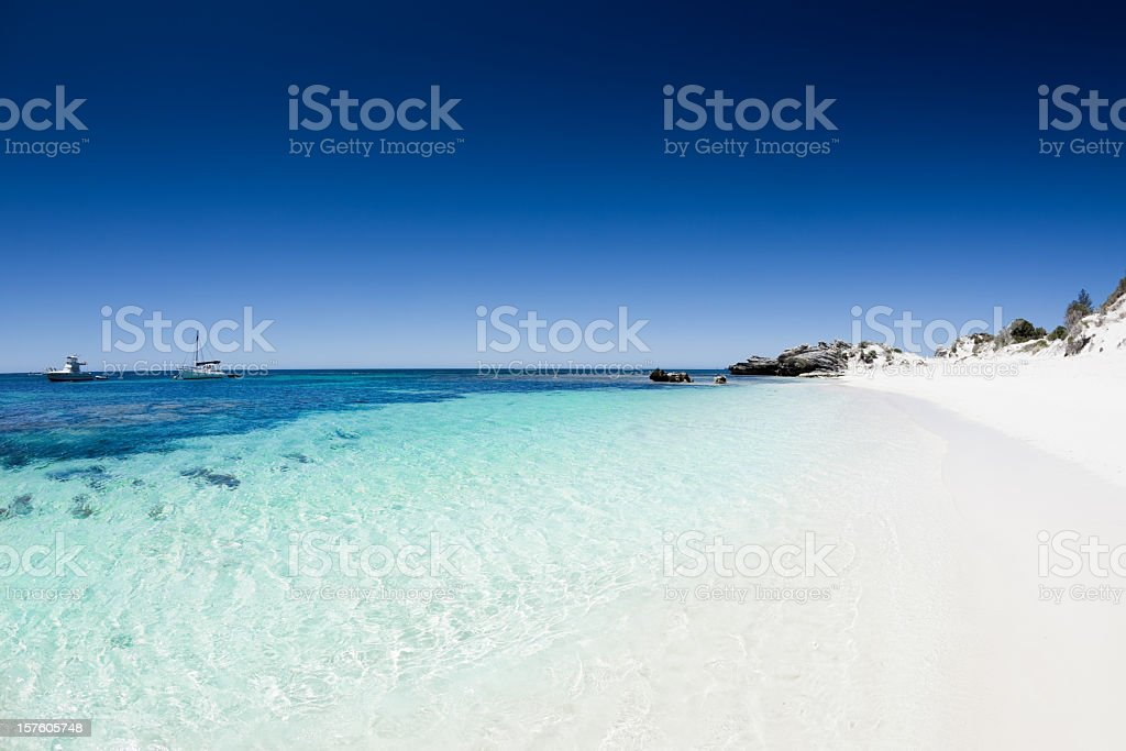 Beach with white sand and clear blue water and sky stock photo