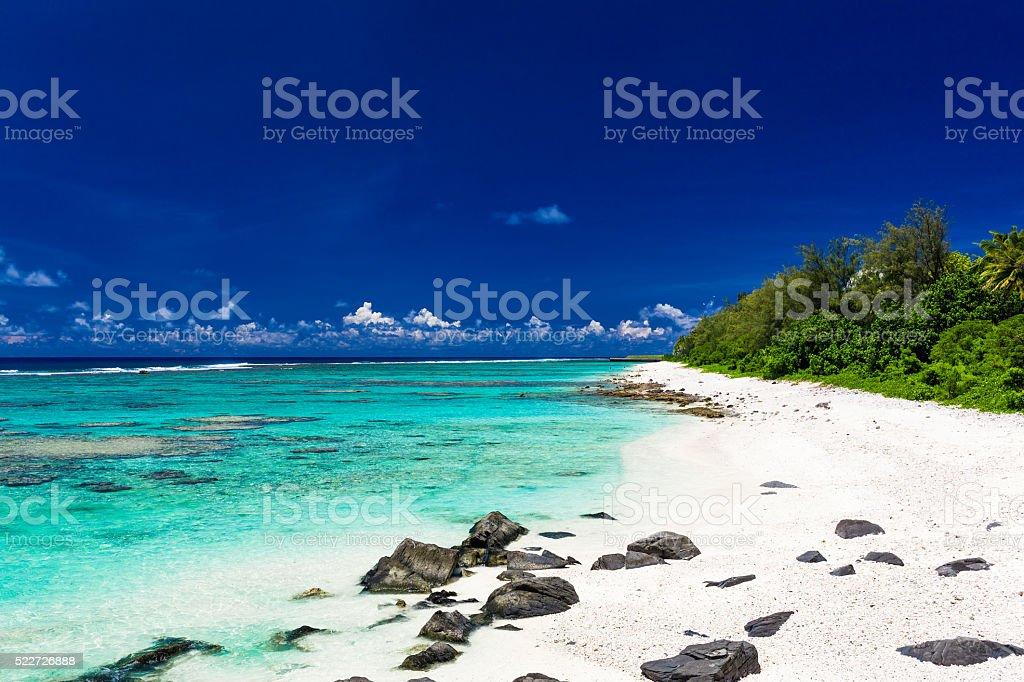 Beach with white sand, black rocks on Rarotonga, Cook Islands stock photo