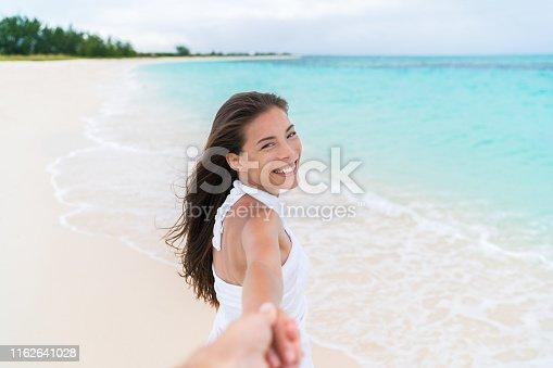 istock Beach woman looking at boyfriend holding hand on honeymoon vacation 1162641028