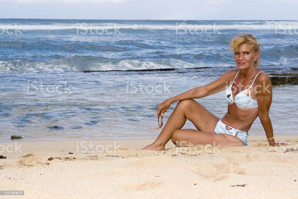 Beach woman Mature woman sitting on a beach on the island of Maui. 50-59 Years Stock Photo