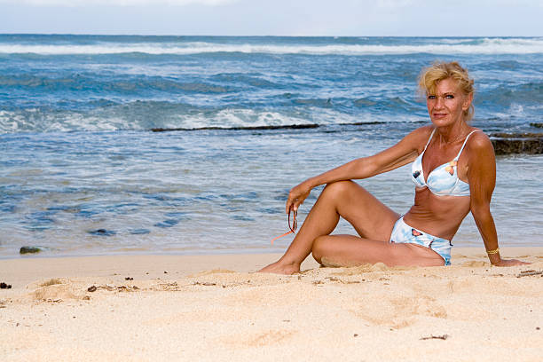 Beach woman Mature woman sitting on a beach on the island of Maui. middle aged women in bikinis stock pictures, royalty-free photos & images