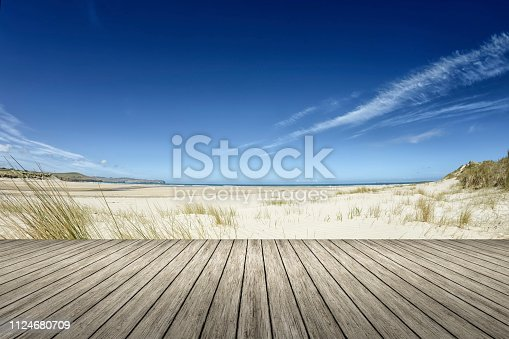 An image of a beach and a wooden jetty in the forground