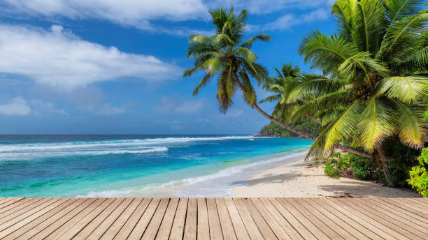 Beach wooden table and coconut palms with party on tropical beach background. stock photo