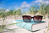 sunglasses on a novel in the dune