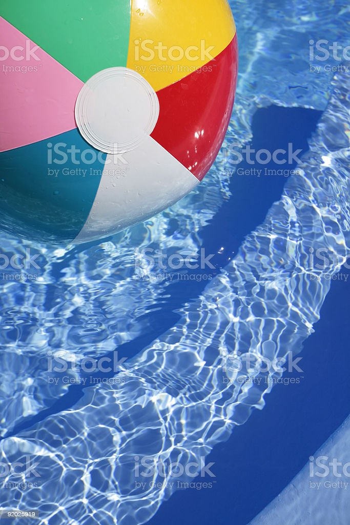 Beachball in a beautiful blue swimming pool royalty-free stock photo