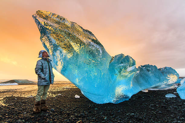 Beached Ice Tourist Extremely beautiful young man posing next to a very big chunk of beached ice near Jokulsarlon, Iceland, at sunset jokulsarlon stock pictures, royalty-free photos & images